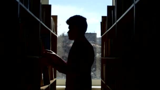 Silueta mladý student čtení knihy v knihovně