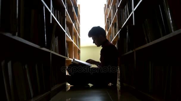 Silueta vysokoškolský student sedí na podlaze v knihovně