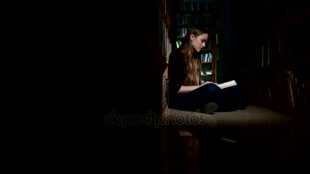 student girl sitting on floor and examines book in library, camera moves left to right