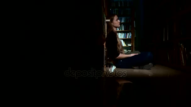 student girl sitting on floor and reading book in library