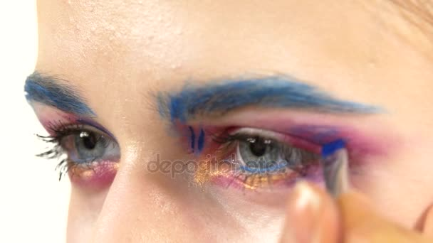 Eye make-up woman applying eyeshadow, making exotic, one, blue eyebrow, yellow shadow, mascara, finishing touch, close up, on white