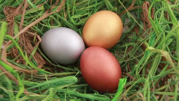 Tři zlaté velikonoční vajíčka na trávě