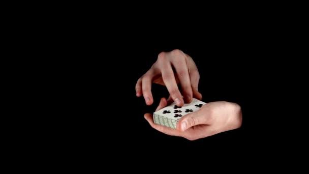 Trik, kouzelník s kartami - změnou karty na černém pozadí, zblízka, boční pohled