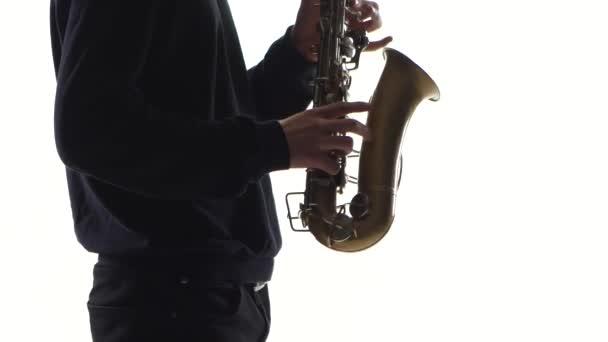 Zenész egy régi szaxofonon játszik. Közelkép a fehér háttér