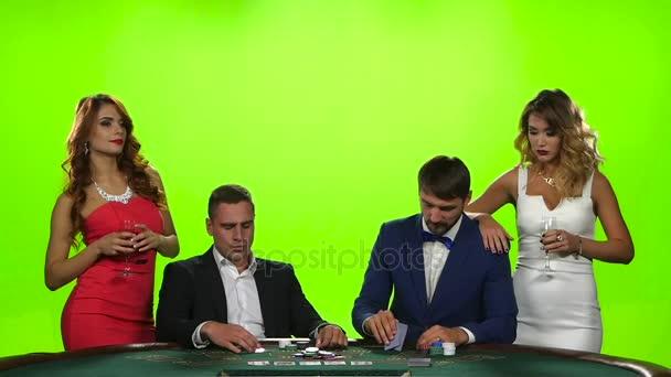 zwei Paare junger Leute beim Kartenspielen am Pokertisch