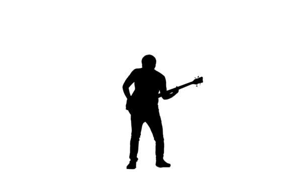 Silueta basový kytarista. Vyskočí při hře. Zpomalený pohyb