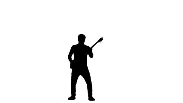 Zpomalený pohyb. Silueta basový kytarista. Vyskočí při hře