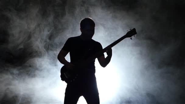 Slow motion. Silhouette bass guitarist man in smoke. Black background