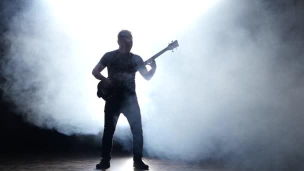 Baskytarista muž v kouři. Zpomalený pohyb. Černé pozadí