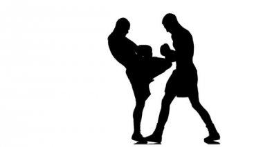 Kickboxers splnit kop kolenem k tělu. Černá silueta