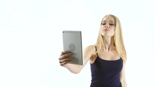 Blond dívka model dělá selfie fotografie na tabletu. Studio