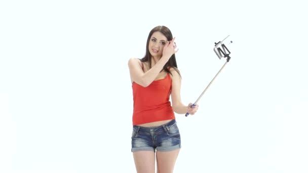 Dívka z modelu vzhled dělá pomocí monopod selfie fotografie