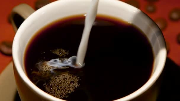 V šálku s horkou černou kávu si mnoho mléka. Closeup