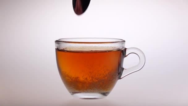 Míchá cukr ve sklenici s čajem lžíce