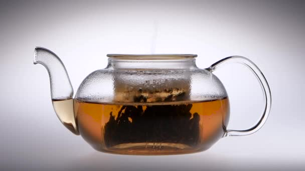 Tea is brewed in a glass teapot. Slow motion. Studio