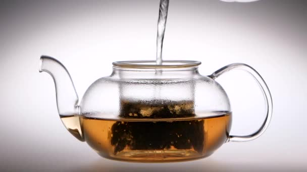 Slow motion. Tea is brewed in a glass teapot. Studio