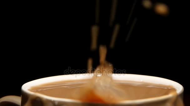 V poháru latte kapky kus cukru. Zpomalený pohyb
