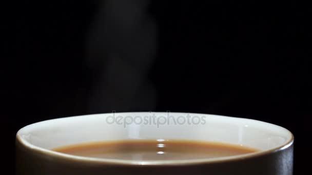 Kus cukru v šálku kávy s mlékem