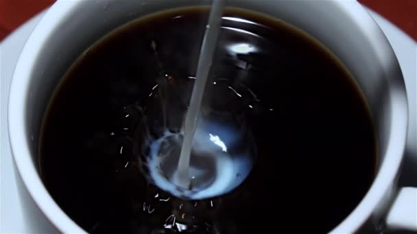 V šálku černé kávy nalila mléko. Pohled shora. Closeup