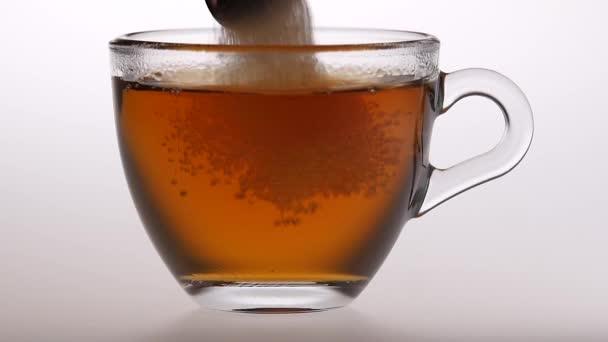 Kanál cukorral keverik egy kicsi csésze teát. Lassú mozgás
