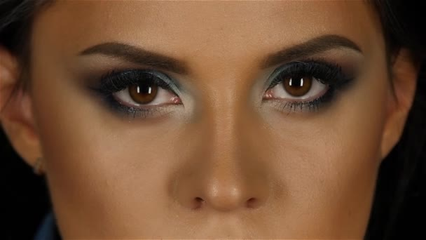 Beautiful girl with makeup breath taking looks straight and blinks his eyes. Close up