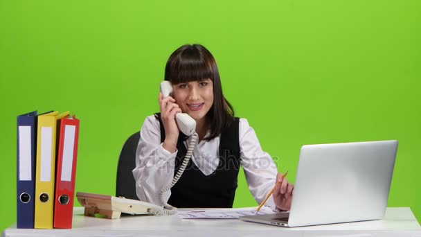 Woman talking by telephone from her office. Green screen