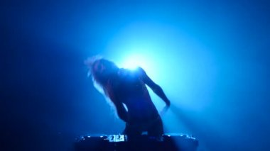 Blonde girl DJ plays track and erotically dancing