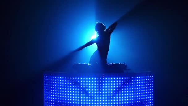 Blond girl dj sexy dancing in blue silhouette. Slow motion