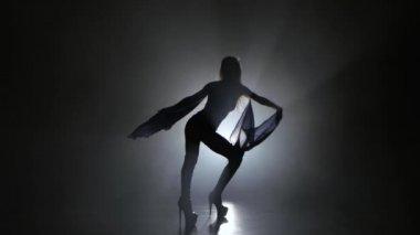 Woman sexually dancing on dark background studio with smoke