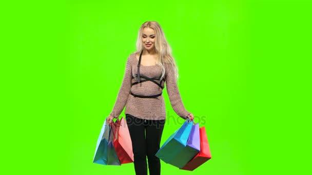 Dívka v krásných šatech nese spoustu barevných balíčků. Zelená obrazovka