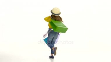Little girl spinning with bags in their hands and behave affectedly. White background. Slow motion