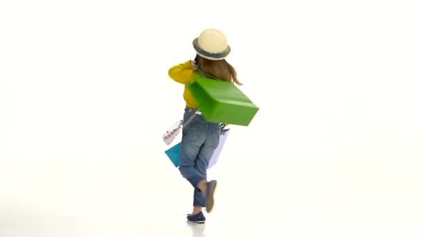 kleines Mädchen, das mit Tüten in der Hand dreht und sich liebevoll benimmt. weißer Hintergrund. Zeitlupe