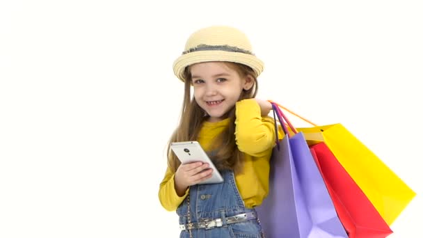 Shopping Little girl holding a mobile phone bags and looking at him and smiling. Slow motion