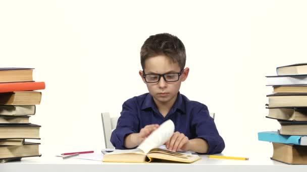 Kluk sedí u stolu, listovat v knize. Bílé pozadí