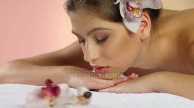 Woman quietly resting after spa procedures lying in orchid flowers