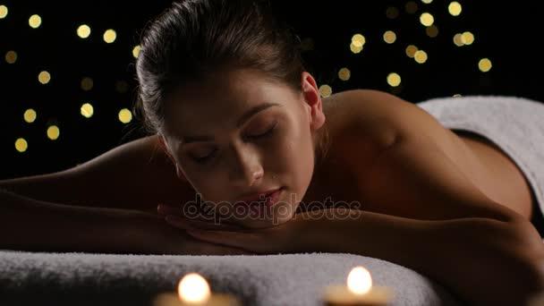 Barna nő pihenő után spa kezelések égő gyertyát. Stúdió