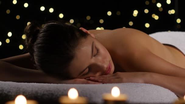 Dívka odpočívá v pokoji s hořící svíčky a tmavým pozadím