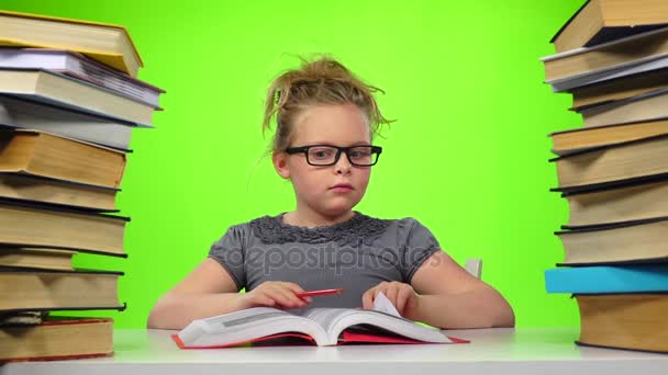 Girl leafing through the pages of books carefully. Green screen. Slow motion