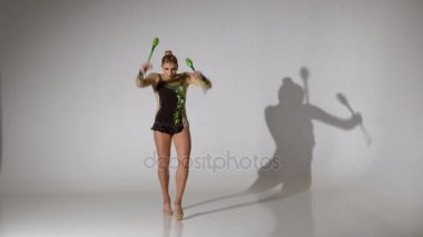 Rhythmic gymnast kneeling and holding her mace it makes acrobatic movements. White background