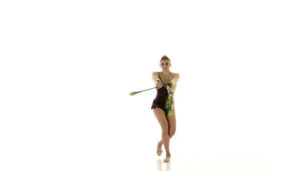 Girl gymnast with mace in hand revolve around him. White background