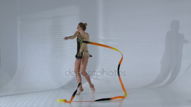 Gymnast whirl with ribbon and stand on the leg. White background