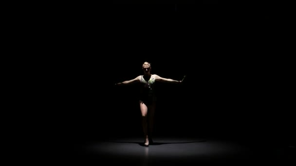 Girl gymnast doing acrobatic movement with a mace in his hand. Black background