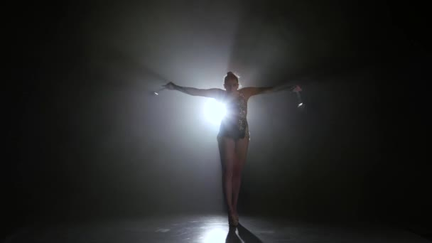 Girl gymnast with mace in hand revolve around him. Black background. Light rear. Silhouette