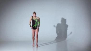 Rhythmic gymnast kneeling and holding her mace it makes acrobatic movements. White background. Slow motion