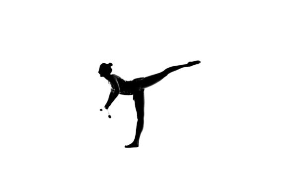Gymnast standing on one leg and holds a mace in his hand. White background. Silhouette. Slow motion