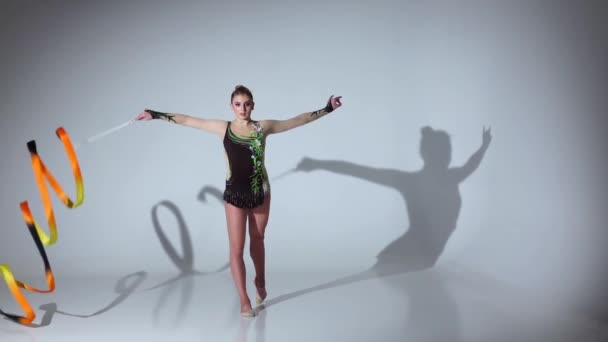 Ritmikus tornász csinál akrobatikus mozog a szalag. Fehér háttér. Lassú mozgás