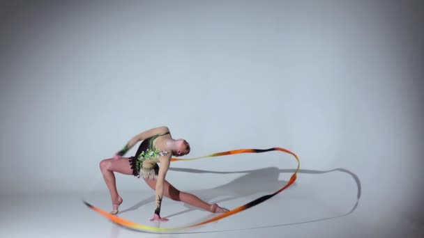 Rhythmic gymnast sit on one leg on the string. White background. Slow motion