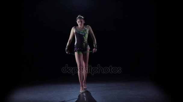 Rhythmic gymnast throws mace up and catches her. Black background. Slow motion