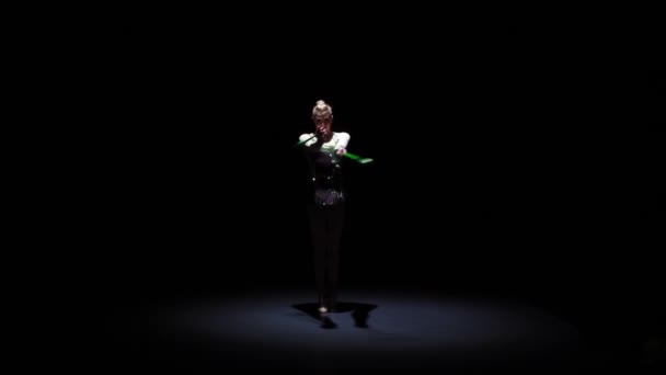 Girl gymnast doing acrobatic movement with a mace in his hand. Black background. Slow motion