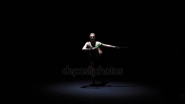 Rhythmic gymnast throws mace up and catches her. Black . Slow motion